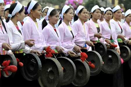 The Muong women wear traditional costume and play gong